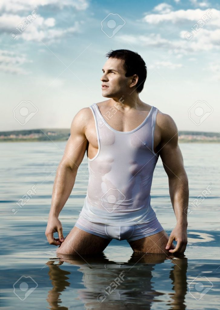 12466135-the-very-muscular-handsome-sexy-guy-on-sky-and-sea-background-stock-photo